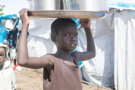 Criança carrega água em um local de proteção civil de Tomping, Sudão do Sul. Foto: ONU/Eskinder Debebe.