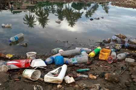 Garrafas de plástico e resíduos de lixo as margens de um rio. Foto: ONU/Martine Perret.